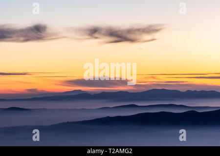Trees silhouettes against a beautifully colored sky at dusk, with mountains layers. - Stock Image