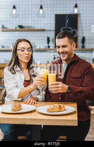beautiful brunette woman and handsome man sitting at table with croissants and clinking glasses with juice in coffee house - Stock Image