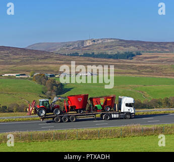 Low-loader HGV carrying farm equipment. M6 Northbound carriageway, Shap, Cumbria, England, United Kingdom, Europe. - Stock Image