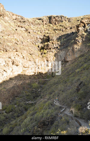 Couple on the footpath along the gorge called the Barranco del Infierno, Adeje, Tenerife. - Stock Image