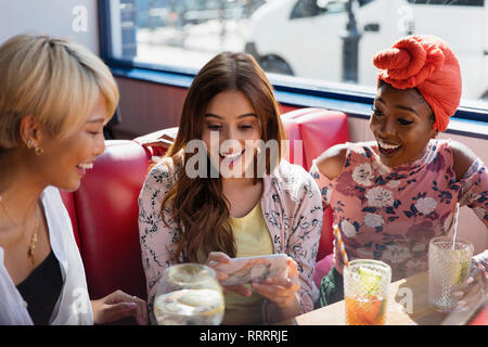 Young women friends using smart phone and drinking cocktails in restaurant - Stock Image
