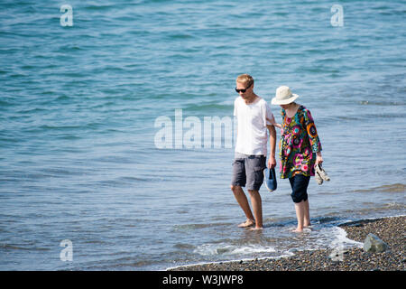 Aberystwyth Wales UK, Tuesday 16 July 2019 UK Weather: A couple walking in the shallow water at the seaside in Aberystwyth on a beautifully warm summers day in west Wales. photo Credit: keith morris/Alamy Live News - Stock Image