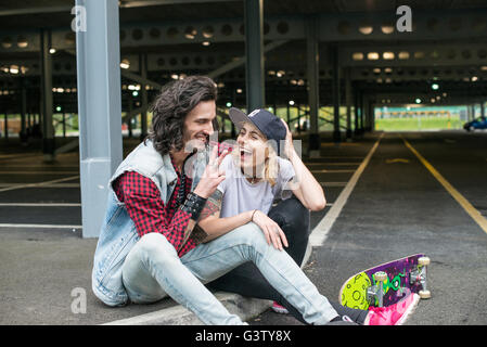 A cool young couple cuddling. - Stock Image
