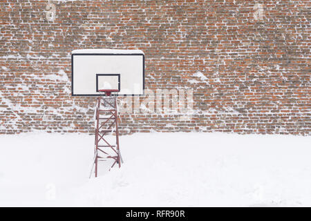 Basketball hoop in the winter, covered with snow. - Stock Image