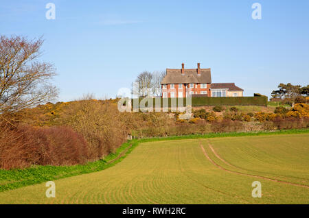 A circular public footpath by a field edge with large thatched house in the Downs at Blakeney, Norfolk, England, United Kingdom, Europe. - Stock Image