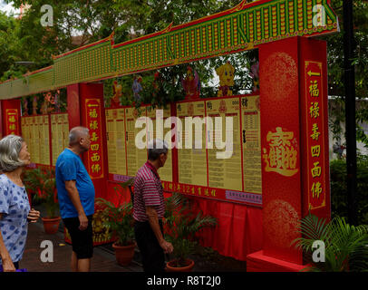 Local Chinese Singaporeans read their daily horoscope at Bugis Junction market, Singapore, Asia - Stock Image