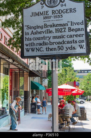 ASHEVILLE, NC, USA-10 JUNE 18:  A mountain fiddler plays for tips on the street, beneath a sign commemorating country singer Jimmie Rodgers. - Stock Image