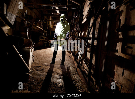 Gas masked person in dark holding a large wrench - Stock Image