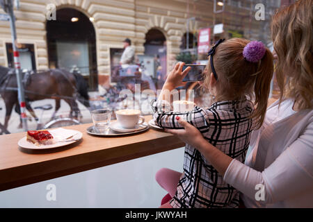 Young mother and daughter spending time in cafe and making photos - Stock Image