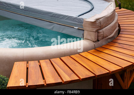 The ultimate garden accessory a free standing cedar wood and leather circular hot tub with cover. - Stock Image