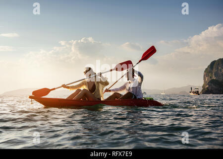 Happy couple walks by sea kayak or canoe at sunset bay. Kayaking or canoeing concept with people - Stock Image