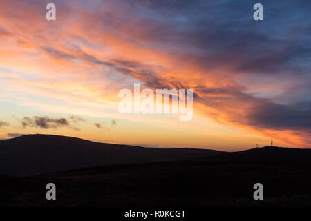 Dramatic sunset over silhouetted Belfast hills. Viewed from summit of Cavehill looking towards Divis Mountain, Belfast, N.Ireland. - Stock Image