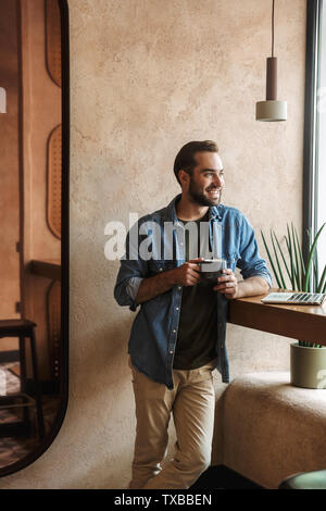 Photo of smiling confident man wearing denim shirt drinking coffee with laptop while working in cafe indoors - Stock Image