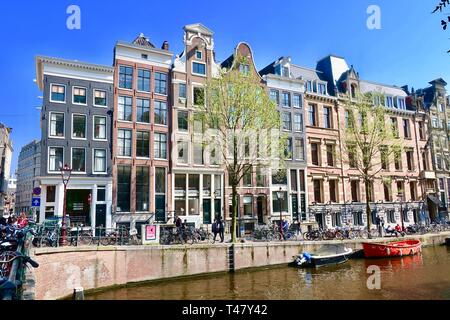 Amsterdam, Netherlands - April 2019: Boats, canals, bikes and tall buildings. - Stock Image