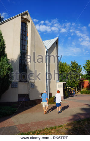Poznan, Poland - July 10, 2018: Older man and woman walking next to a church on the Stare Zegrze district - Stock Image