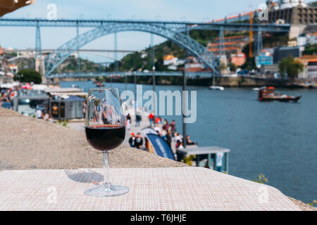 Selective focus of red wine glass overlooking Cais da Ribeira and Ponte de Dom Luis I on the River Douro in Porto, Portugal - Stock Image