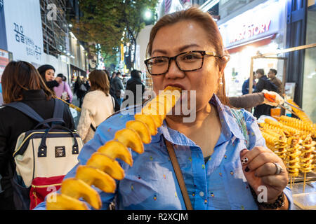 A lady eats a deep fired potato spiral on a stick bought form a street food stall in Myeongdong in Seoul, South Korea. - Stock Image