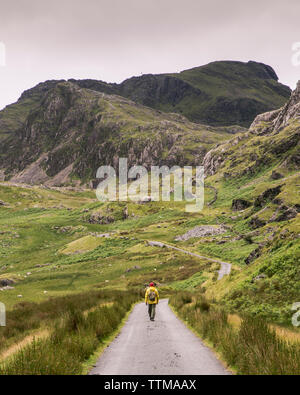 Rear view of man with backpack walking on road amidst mountains against sky - Stock Image