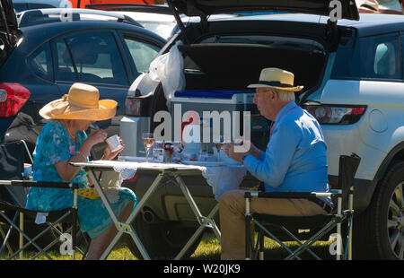 Smart couple enjoy lunch  in the car park at the Henley Royal Regatta, Henley-on-Thames, England, UK - Stock Image