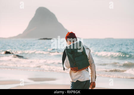 Man backpacker walking alone on sea beach solo traveling summer vacations lifestyle adventure outdoor - Stock Image
