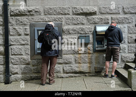 Two men using cash machines in Camborne, Cornwall, UK - Stock Image