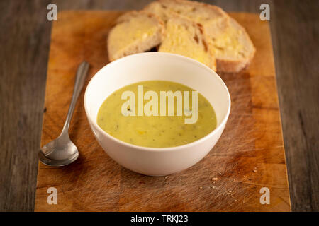 Fresh leek and potato soup in a bowl on a wooden board with crusty white bread and butter - Stock Image
