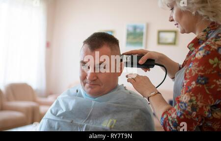 International Space Station Expedition 59 crew member Alexey Ovchinin of Roscosmos has his hair cut by a stylist at the Baikonur Cosmodrome March 12, 2019 in Baikonur, Kazakhstan. Expedition 59 crew: Christina Koch of NASA, Alexey Ovchinin of Roscosmos, and Nick Hague of NASA will launch March 14th onboard the Soyuz MS-12 spacecraft for a six-and-a-half month mission on the International Space Station. - Stock Image