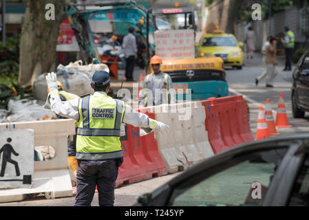 A traffic control person directs cars around a road works site in central Singapore - Stock Image