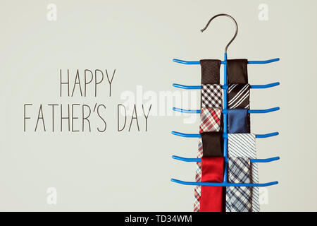 the text happy fathers day and a necktie hanger with some neckties of different colors and patterns, on an off-white background - Stock Image