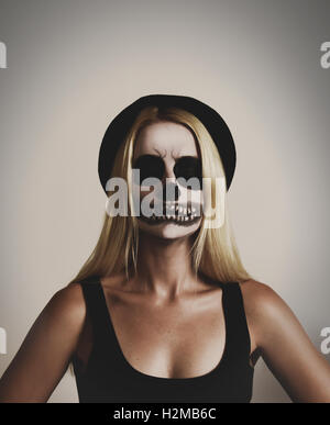 A young woman is wearing a scary skelton makeup mask with black and white paint on an isolated background for a - Stock Image