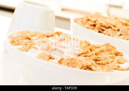 closeup of a bowl with breakfast cereals soaked in milk or drinkable yogurt, on a table set for breakfast - Stock Image