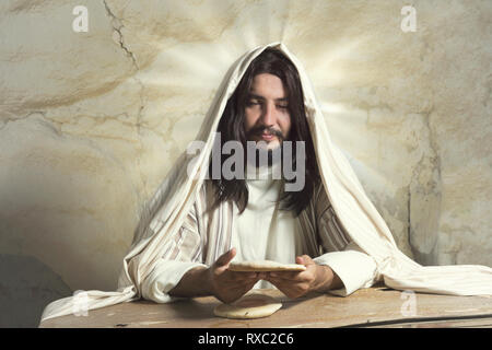Authentic reenactment scene of Jesus breaking the bread during Last Supper, saying 'this is my body'. - Stock Image