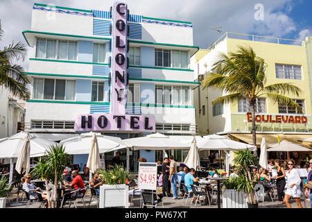 Miami Beach Florida Ocean Drive New Year's Day Art Deco District Colony Hotel landmark sidewalk cafe restaurant umbrellas alfr - Stock Image