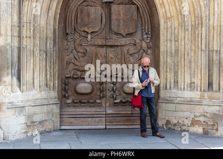 Man stood next to the carved wooden doors of Bath Abbey using a mobile phone - Stock Image