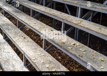 Empty wooden seats in a diagonal composition with nobody in the scene. Autumn leaves cover the wood seats. - Stock Image