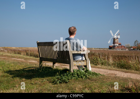 Man sitting on bench on the edge of the marshes with Cley Windmill in the background, Cley next the Sea, Norfolk - Stock Image