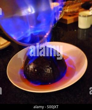 Flambé of Christmas pudding in the kitchen on Christmas Day. - Stock Image