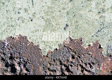 Rust breaks through aged green paint covering the old aged metal beneath the surface copy space area for repair - Stock Image