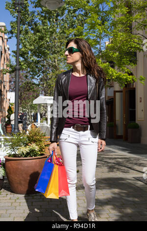 adult brown hair woman with white jeans, red shirt, leather blazer jacket and green sunglasses holding blue, red and yellow shopping bags walking at u - Stock Image