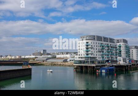 Brighton Marina Views UK - Small boat arrives past new apartments - Stock Image