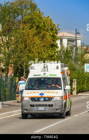 GARDA, LAKE GARDA, ITALY - SEPTEMBER 2018:  Ambulance with blue lights flashing on an emergency call driving through the town of Garda on Lake Garda. - Stock Image