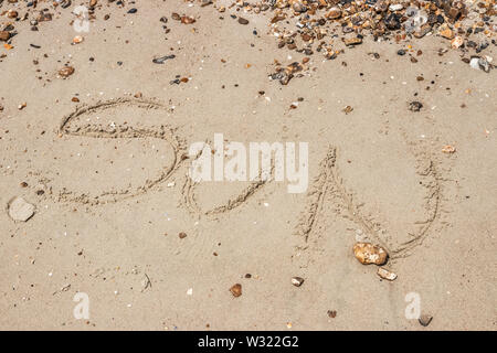 The word sun written in sand on a beach - Stock Image