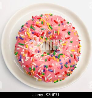 Top down view of a pink sprinkle donut. - Stock Image