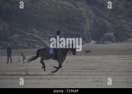 Perranporth, Cornwall,UK. 31st March 2019. UK Weather. It was hot and sunny for the first day of British Summertime on the beach at Perranporth, with horse riders, dog walkers and families out making the most of the hot weather on mothers day. Credit: Simon Maycock/Alamy Live News - Stock Image