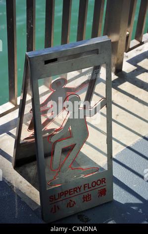 Slippery floor warning sign at the Star Ferry Pier, Hongkong CN - Stock Image