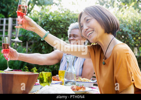 Happy active senior women toasting rose wine at garden party - Stock Image