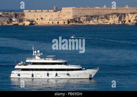 The 35m Heesen luxury yacht Alcor in Malta's Grand Harbour, with Fort Ricasoli in the distance guarding the port entrance - Stock Image