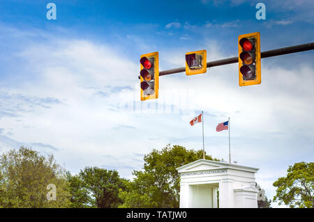 Red traffic light above Canada and USA flags on top of Peace Arch Monument at international border between the two countries near Vancouver, BC. - Stock Image