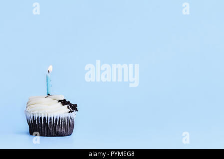 Pretty chocolate flavored cupcake with vanilla buttercream frosting decorated with white chocolate shavings, chocolate chips and one candle burning. F - Stock Image