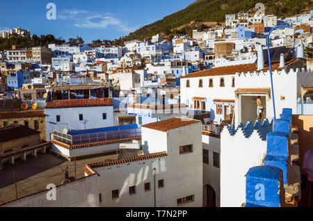 Chefchaouen, Morocco : A man paints a house surrounded by the rooftops of the medina old town, well noted for its blue-washed architecture. - Stock Image